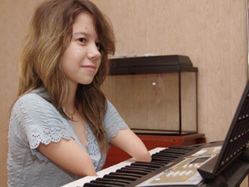 Девочка без ног и рук играет и поёт (видео)