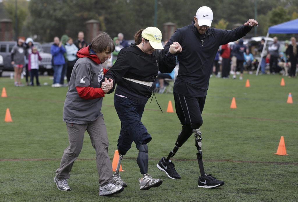 Селеста Коркоран в своей желтой бейсбольной кепке «Бостон силен» идет по полю, поддерживаемая под руки. У одного из ее помощников обе ноги на протезах.